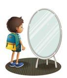 Un ragazzo che affronta lo specchio Immagine Stock