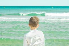 Un ragazzo che esamina il mare con il suo di nuovo alla macchina fotografica Bambino che esamina il mare Immagine Stock
