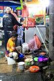 Un ragazzo che lava i piatti dal lato della strada Immagini Stock Libere da Diritti