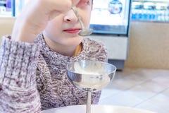 Un ragazzo che mangia gelato dal vaso del metallo in self-service fotografia stock
