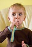 Un ragazzo che mangia i lecca lecca della gelatina Fotografia Stock