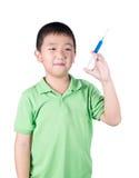Un ragazzo che porta maglietta verde, tenente siringa in sua mano fotografia stock libera da diritti