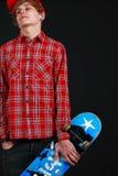 Un ragazzo che sembra freddo con un pattino Fotografia Stock Libera da Diritti