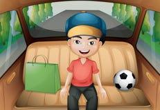 Un ragazzo che si siede dentro un'automobile corrente Immagini Stock