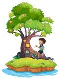 Un ragazzo che si siede sopra le radici di un albero ha stupito dalla capanna sugli'alberi Immagini Stock