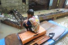 Un ragazzo che si siede su una barca nell'inondazione immagini stock