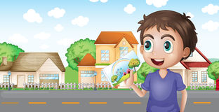 Un ragazzo che tiene un'immagine davanti alle case vicino alla strada Fotografie Stock