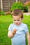 Un ragazzo che tiene uovo crudo immagine stock libera da diritti