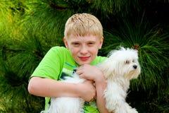 Un ragazzo con un cane di bianco dell'animale domestico fotografia stock