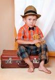 Un ragazzo con un orso di orsacchiotto che si siede su una valigia. Immagini Stock