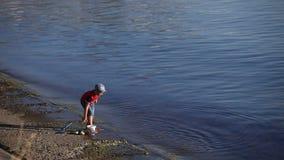 Un ragazzo con una rete e un secchio sulla riva video d archivio