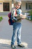 Un ragazzo con uno zaino, i libri e un globo va a scuola dopo un'estate lunga Immagine Stock Libera da Diritti