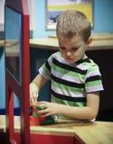Un ragazzo costruisce Lego Structure al museo del ` s dei bambini di scoperta immagine stock libera da diritti