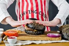 Un ragazzo dai capelli rossi attraente nel grembiule di un cuoco unico sta cucinando un hamburger nella cucina Ricetta per la cot fotografie stock