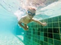 Un ragazzo del bambino sta nuotando underwater in uno stagno, sta sorridendo e trattenendo il respiro, con i vetri di nuoto immagine stock libera da diritti
