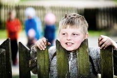 Un ragazzo del villaggio dietro la rete fissa Fotografia Stock