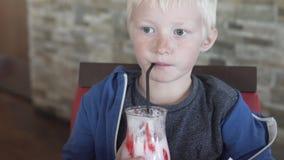 Un ragazzo dell'albino beve un frappé ad un caffè video d archivio