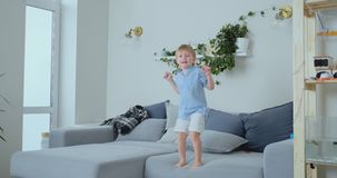 Un ragazzo di 4 anni con capelli bianchi ed i salti blu ed i sorrisi di una camicia sul sofà Divertimento e bambino a casa Scher video d archivio