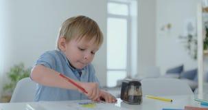 Un ragazzo di 4 anni si siede a casa alla tavola nel salone ed estrae le matite di colore su carta video d archivio