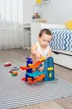 Un ragazzo di cinque anni che giocano le automobili del giocattolo e una strada Immagini Stock