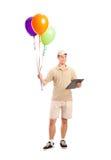 Un ragazzo di consegna che trasporta gli aerostati Immagini Stock