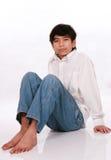 Un ragazzo di dodici anni che si siede sul pavimento Immagine Stock