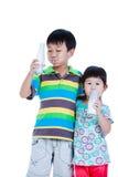 Un ragazzo di due asiatici e latte alimentare della ragazza, isolato su bianco Drinkin Immagine Stock