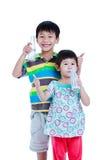 Un ragazzo di due asiatici e latte alimentare della ragazza, isolato su bianco Drinkin Fotografie Stock Libere da Diritti