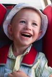 Un ragazzo di risata che si siede in un ripetitore immagine stock libera da diritti