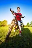 Un ragazzo di sei anni su una bici Fotografie Stock