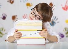 Un ragazzo di sette anni con i libri Di nuovo al banco Fotografia Stock