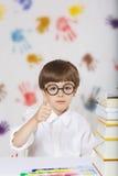 Un ragazzo di sette anni con i libri Di nuovo al banco Immagini Stock