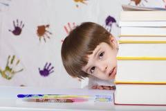 Un ragazzo di sette anni con i libri Di nuovo al banco Fotografie Stock