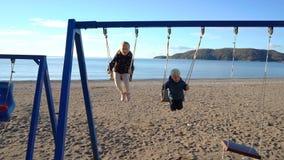 Un ragazzo di tre anni e una ragazza di sei anni che oscillano su un'oscillazione su una mattina soleggiata sulla costa video d archivio