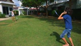 Un ragazzo e una ragazza dell'adolescente giocano il volano su un prato inglese verde nel cortile della loro casa video d archivio