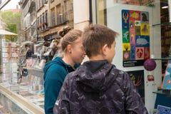 Un ragazzo e una ragazza esaminano i libri in una libreria a Strasburgo immagine stock libera da diritti