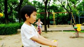 Un ragazzo e una ragazza stanno giocando al campo da giuoco nel parco nel pomeriggio, essi che giocano con la felicità ed allegri video d archivio