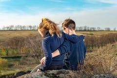 Un ragazzo e una ragazza stanno sedendo su una scogliera, due amici, un fratello e una sorella, sta abbracciando fotografia stock libera da diritti