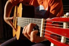 Un ragazzo effettua una canzone con la chitarra Immagine Stock
