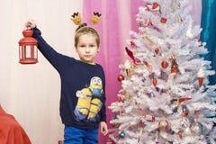 Un ragazzo fa una pausa l'albero di Natale con una lanterna rossa in sua mano Fotografia Stock Libera da Diritti