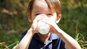 Un ragazzo felice all'aperto ama bere il kefir da un prodotto lattiero-caseario da una tazza di vetro trasparente al rallentatore video d archivio