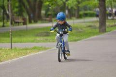 Un ragazzo felice del bambino di 5 anni divertendosi nel parco di primavera con un bicycl Fotografie Stock