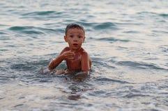 Un ragazzo felice sta giocando nelle onde sulla spiaggia Il ragazzo allegro bagna nelle onde del mare al tramonto immagine stock libera da diritti