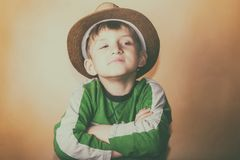 Un ragazzo fiero ed avido in un cappello di paglia con un'espressione facciale altera esamina la macchina fotografica su un fondo fotografia stock libera da diritti