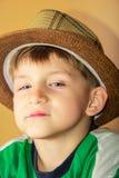 Un ragazzo fiero ed avido in un cappello di paglia con un'espressione facciale altera esamina la macchina fotografica su un fondo fotografie stock
