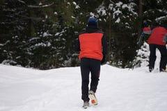 Un ragazzo funziona nella neve senza sciare, alta montagna Fotografie Stock