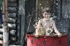 Un ragazzo gioca in acqua Fotografia Stock