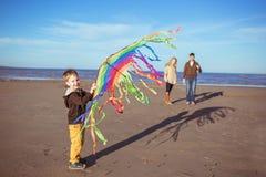 Un ragazzo hollding un aquilone in sue mani Fotografia Stock