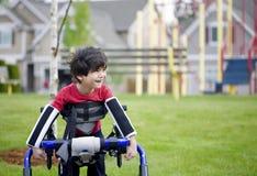 Un ragazzo invalido di quattro anni che si leva in piedi nel camminatore Immagini Stock