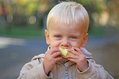 Un ragazzo morde in una mela Immagine Stock